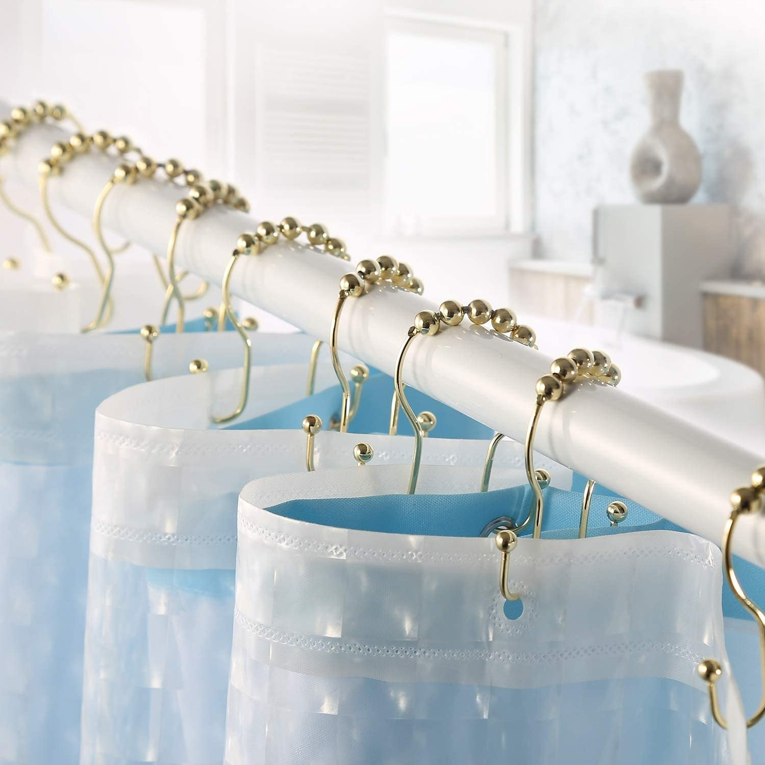 A set of gold shower hooks holding up a shower curtain