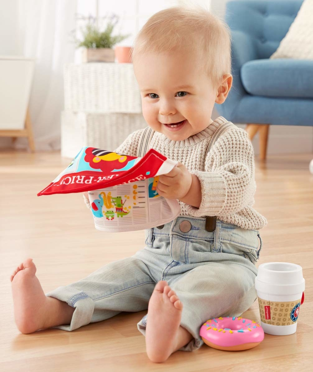 a baby playing with a toy newspaper, donut, and coffee cup