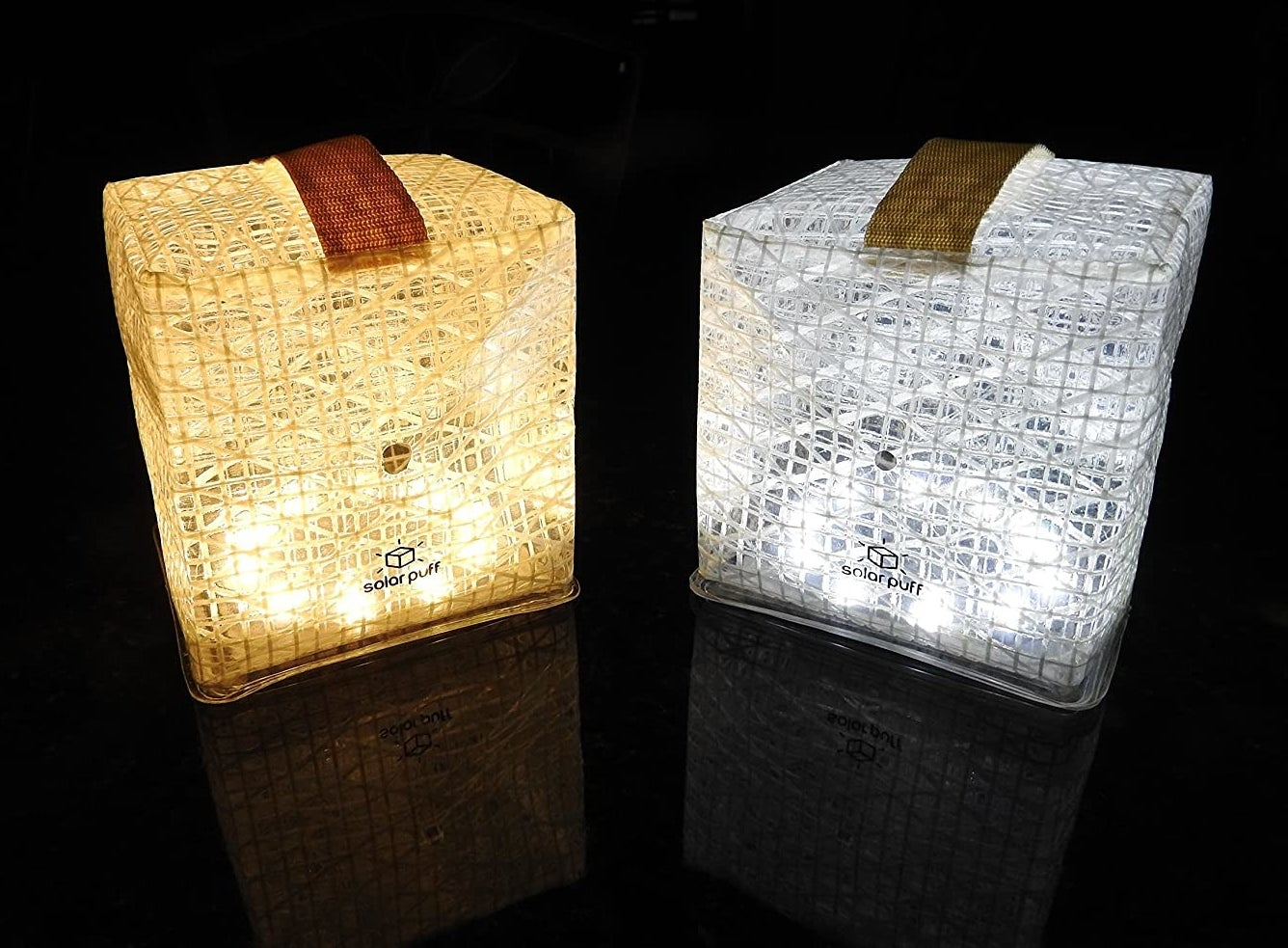 Two solar lights lit up in a dark room