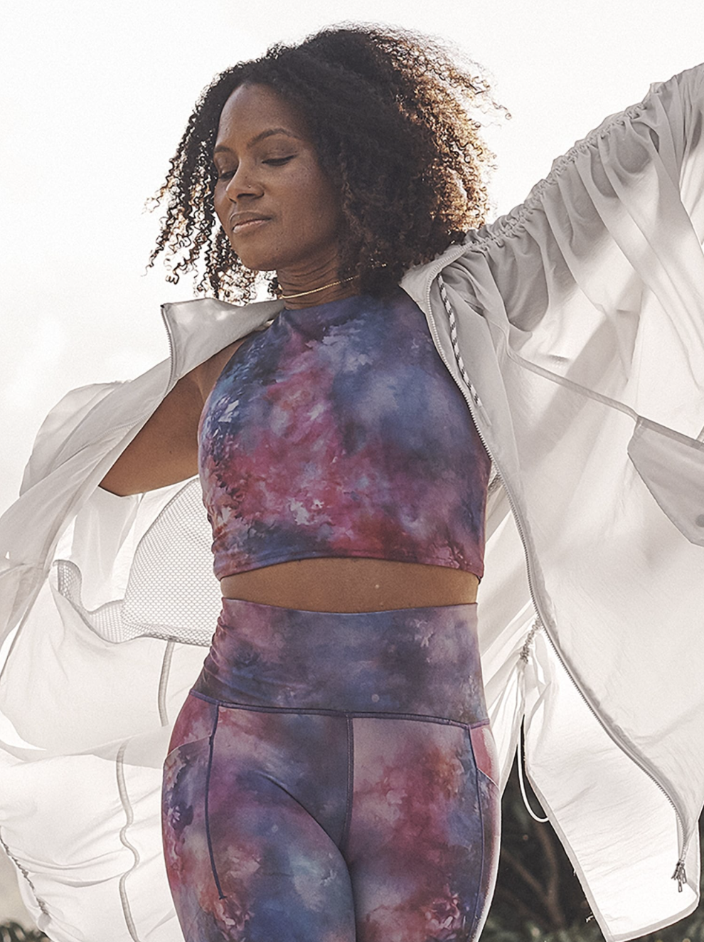 A model wearing the sleeveless crop top with a pink and purple galaxy/tie-dye design