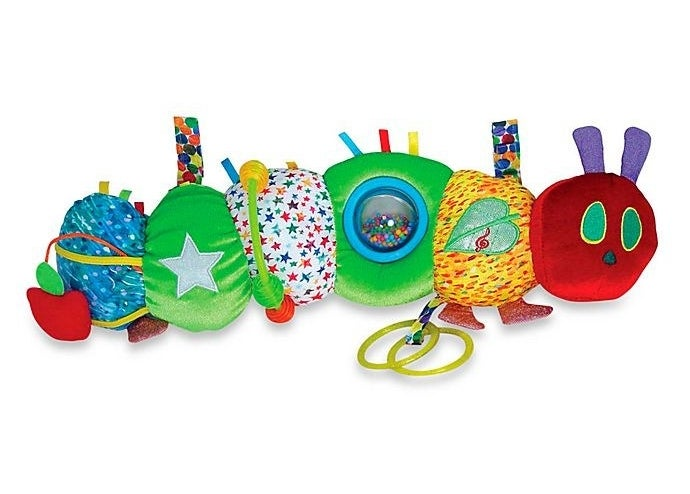 a plush caterpillar-shaped toy with various things for a baby to play with on it