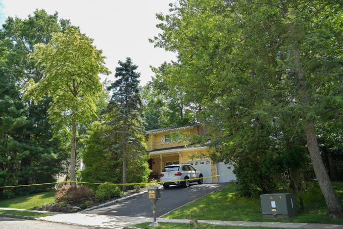 The home of Judge Esther Salas in New Jersey is seen with police tape around it and large trees that surround the property.