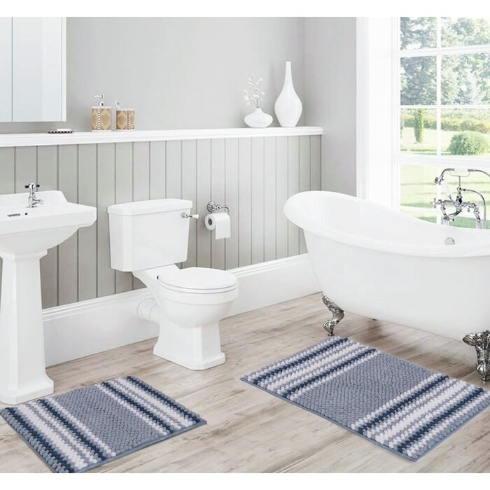 Two bath rugs in different sizes with gray and blue stripes