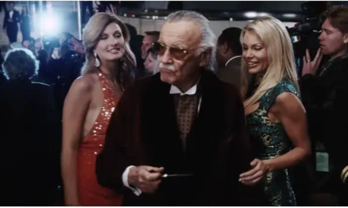 Stan Lee in a tuxedo with beautiful women on his arms
