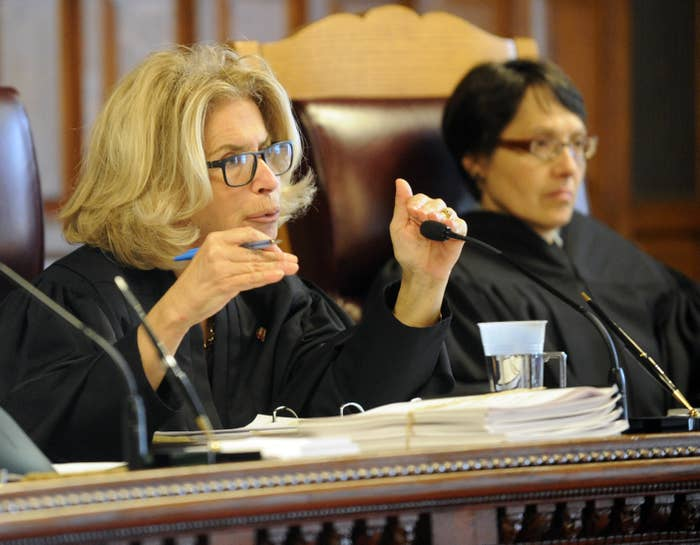 Judge DiFiore wears glasses and gestures with her hands as she speaks into a microphone from the bench in 2016.