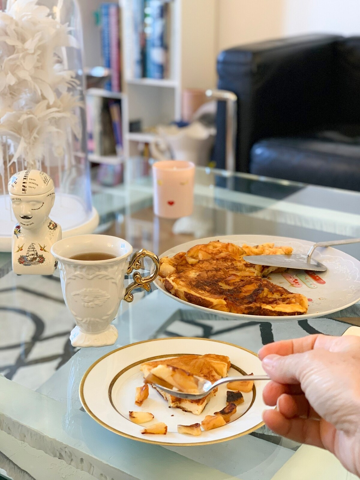 a slice of apple crêpe on fine china next to a cup of tea