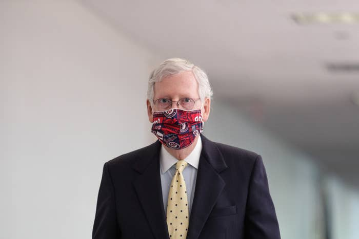 McConnell stands alone in a white hallway wearing a suit and a red-and-blue Washington Nationals-themed mask.