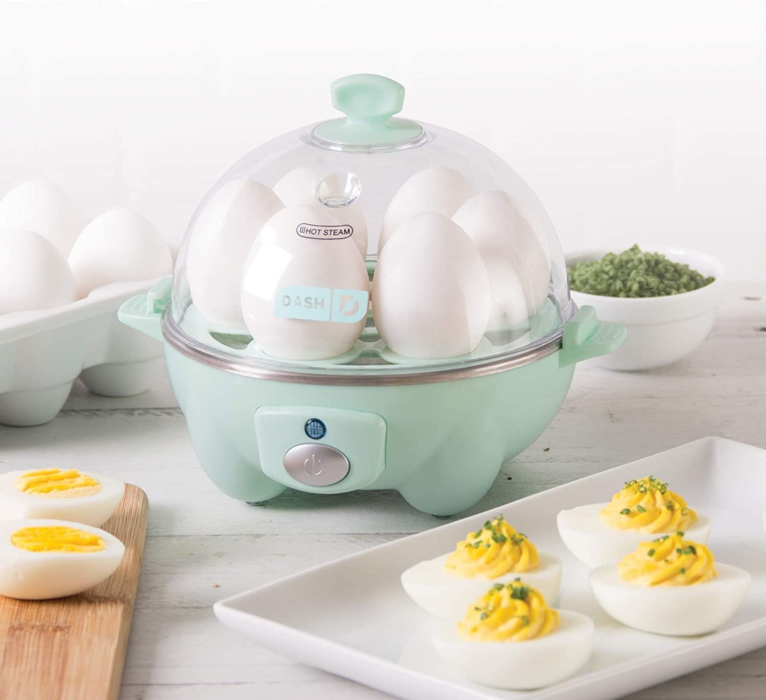 The egg cooker on a countertop next to some devilled eggs