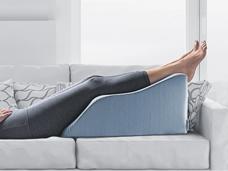 A model lying on the couch with their legs up on the slightly curved wedge cushion in blue