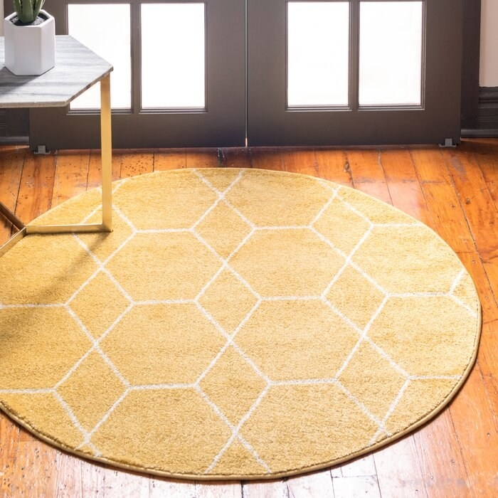 Round Elborough Yellow Rug in a living room