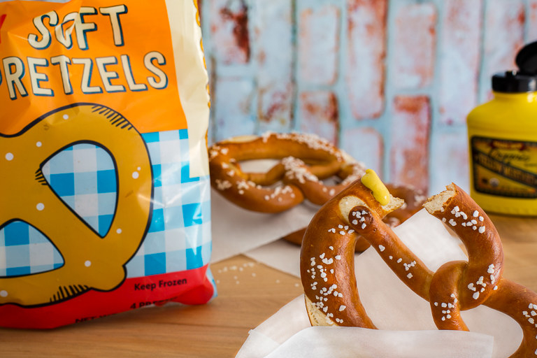 A soft pretzel dipped in mustard, wrapped in parchment paper upon a wooden table