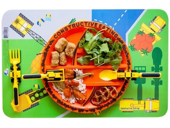"The orange plate with various dividers and ramps and the words ""constructive eating"" on top of the construction site-themed placemat with the yellow, machinery-shaped utensils"