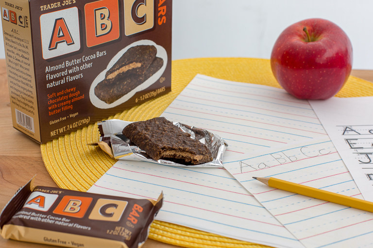 A box of ABC bars, an unwrapped bar sitting in its wrapper, an apple, and some lined writing paper with a pencil