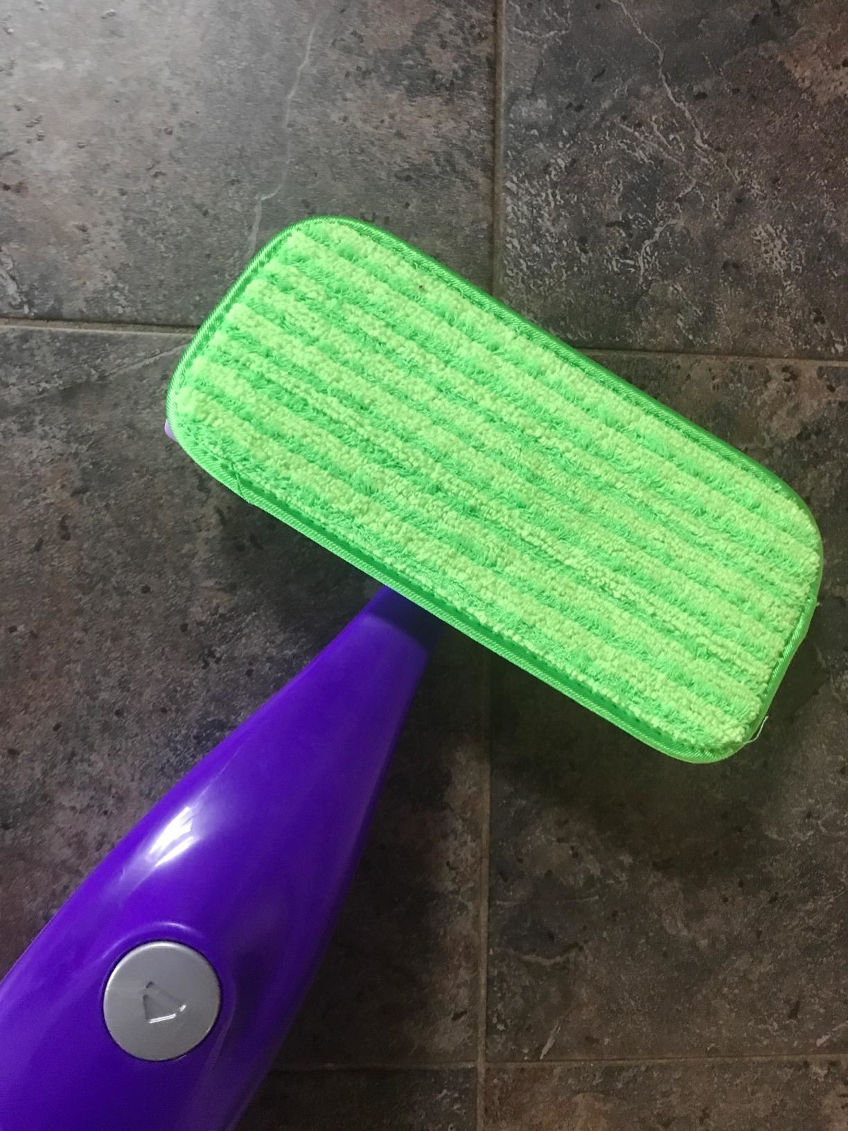 A reviewer's photo of a purple mop handle with the green cleaning pad attached