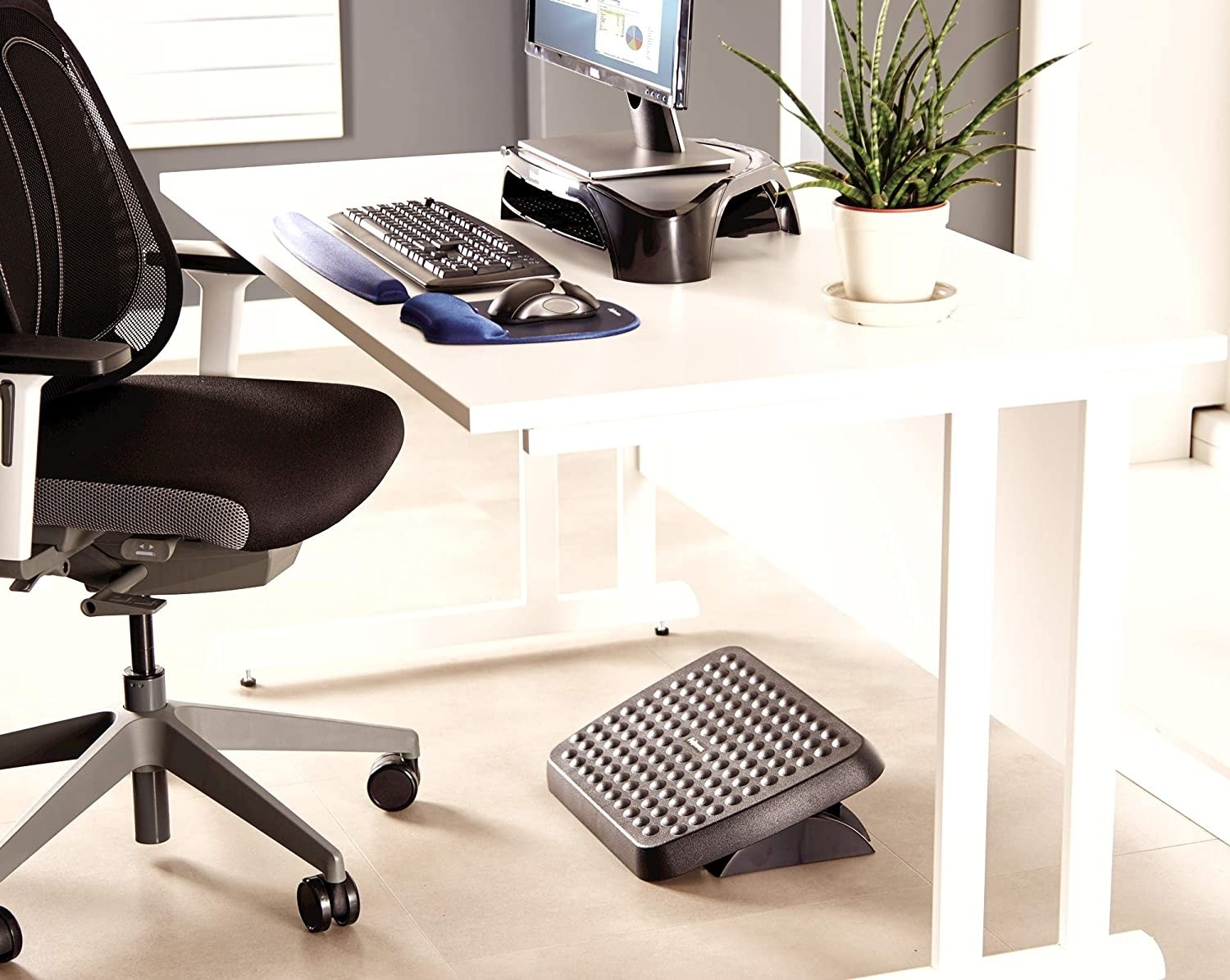 An angled foot rest under a desk with office equipment