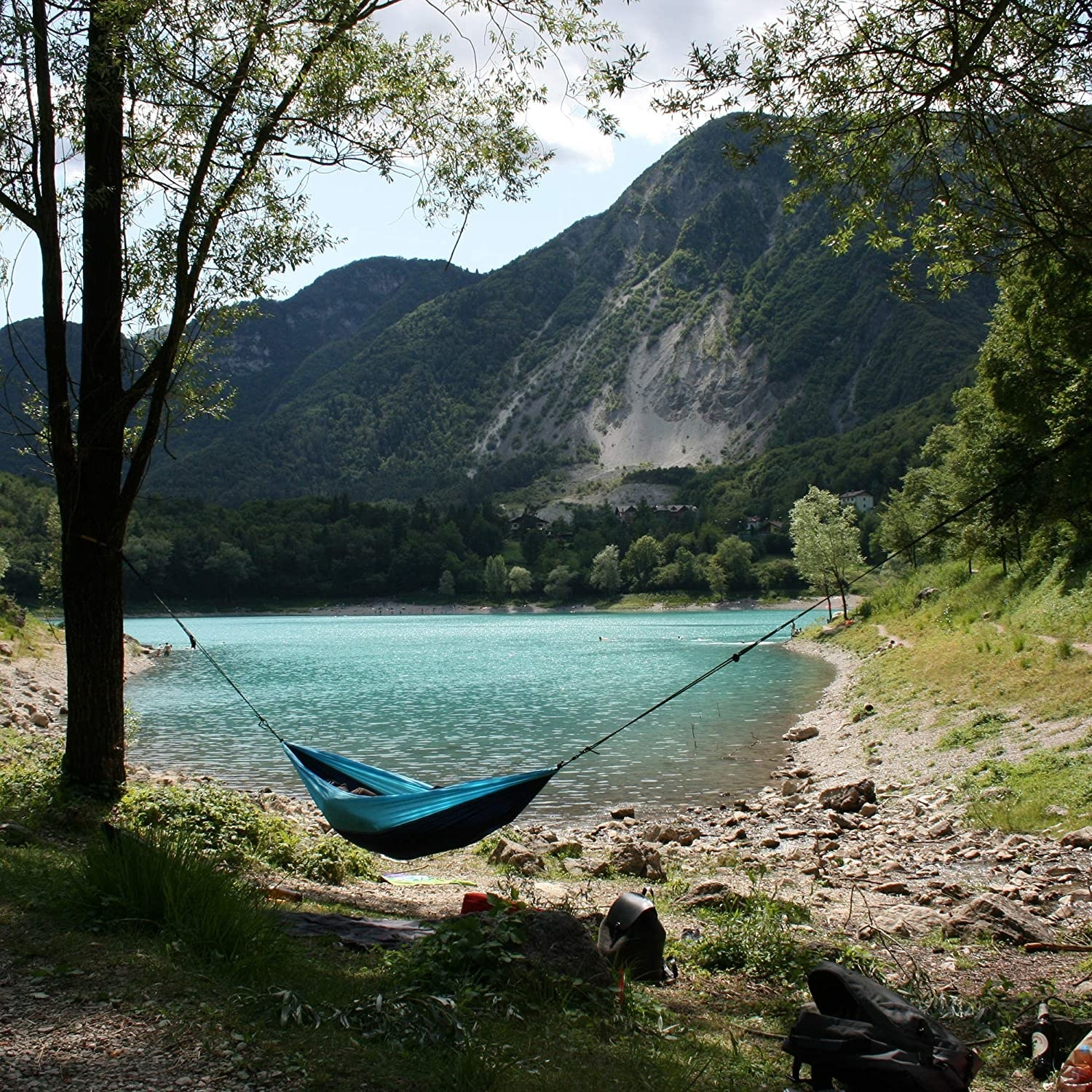 A person napping in the hammock beside a lake