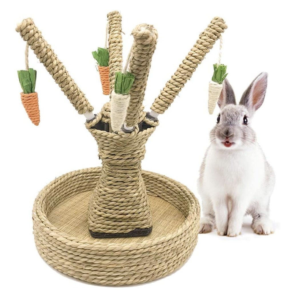 White and gray rabbit sitting beside the woven toy. Four faux carrots dangle down from the center pole.