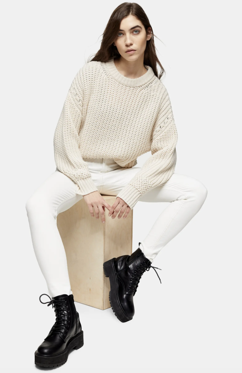 Model wearing the high-waisted skinny jeans  with a white knit sweater and chunky black boots