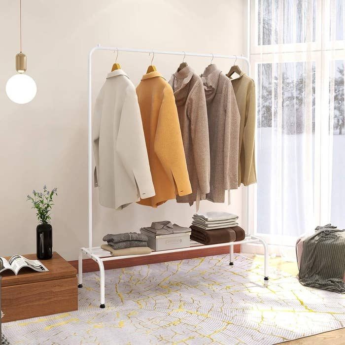 A large metal garment rack with jackets hanging from it There is shelf below that has folded clothes on it