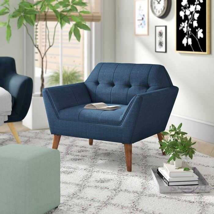 Armchair in upholstered fabric in blue with mid-century wooden legs