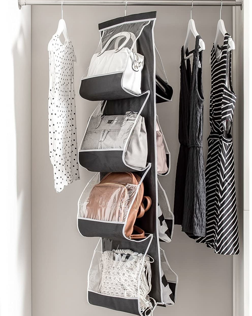 A long fabric handbag organizer hanging from a clothing rod It has four pockets on each side and are filled with large handbags