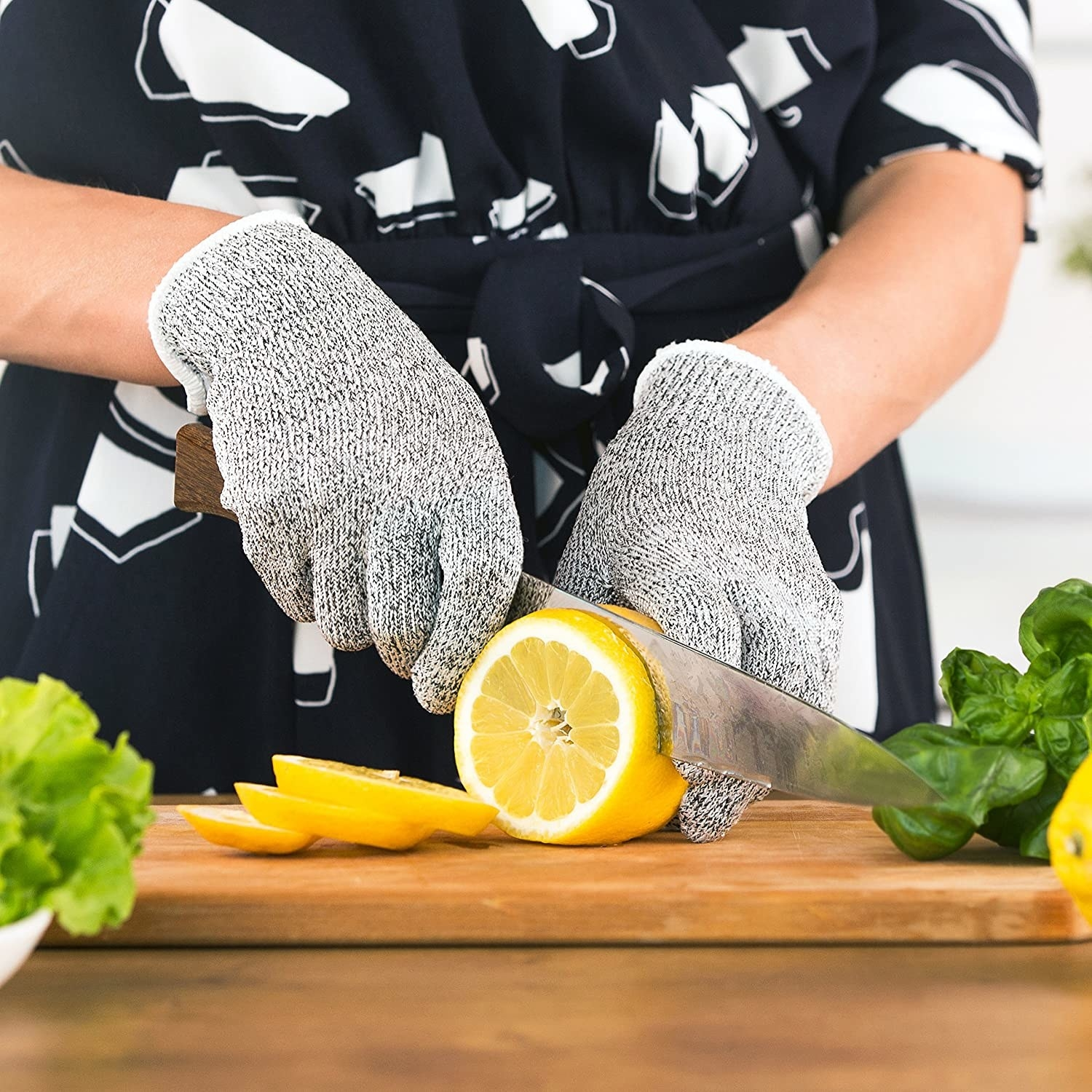 A person cutting a lemon while wearing the gloves