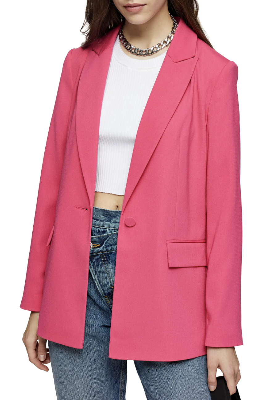 Model wearing the blazer with a single-button closure and flap pockets in bright pink