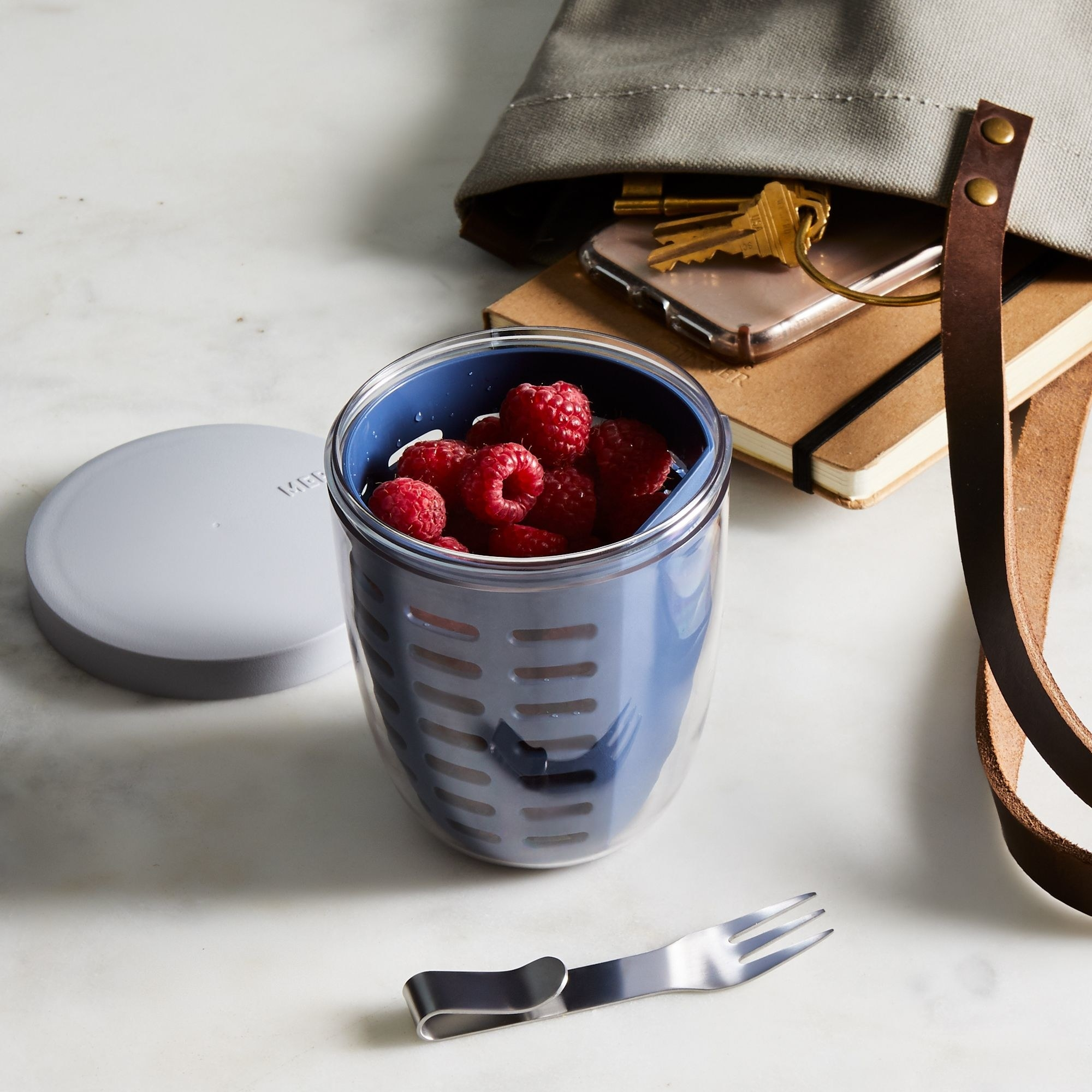raspberries in clear plastic cup with dark blue colander insert and tiny fork
