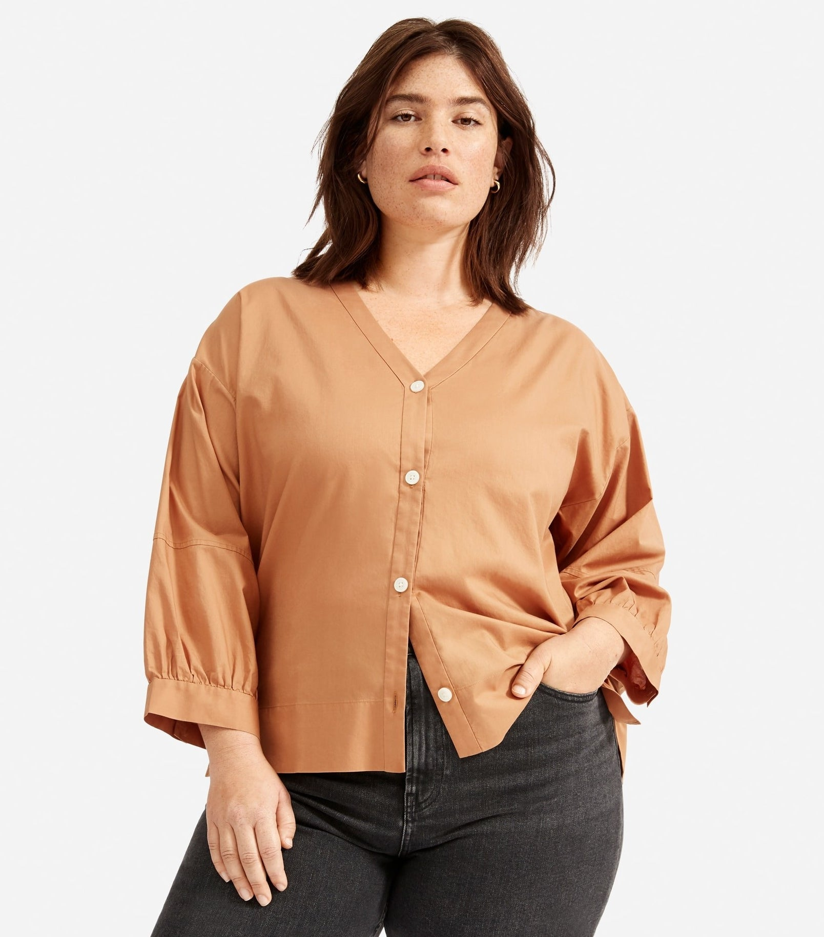 model in light orange button-up top with a V-neck, no collar and slight balloon sleeves