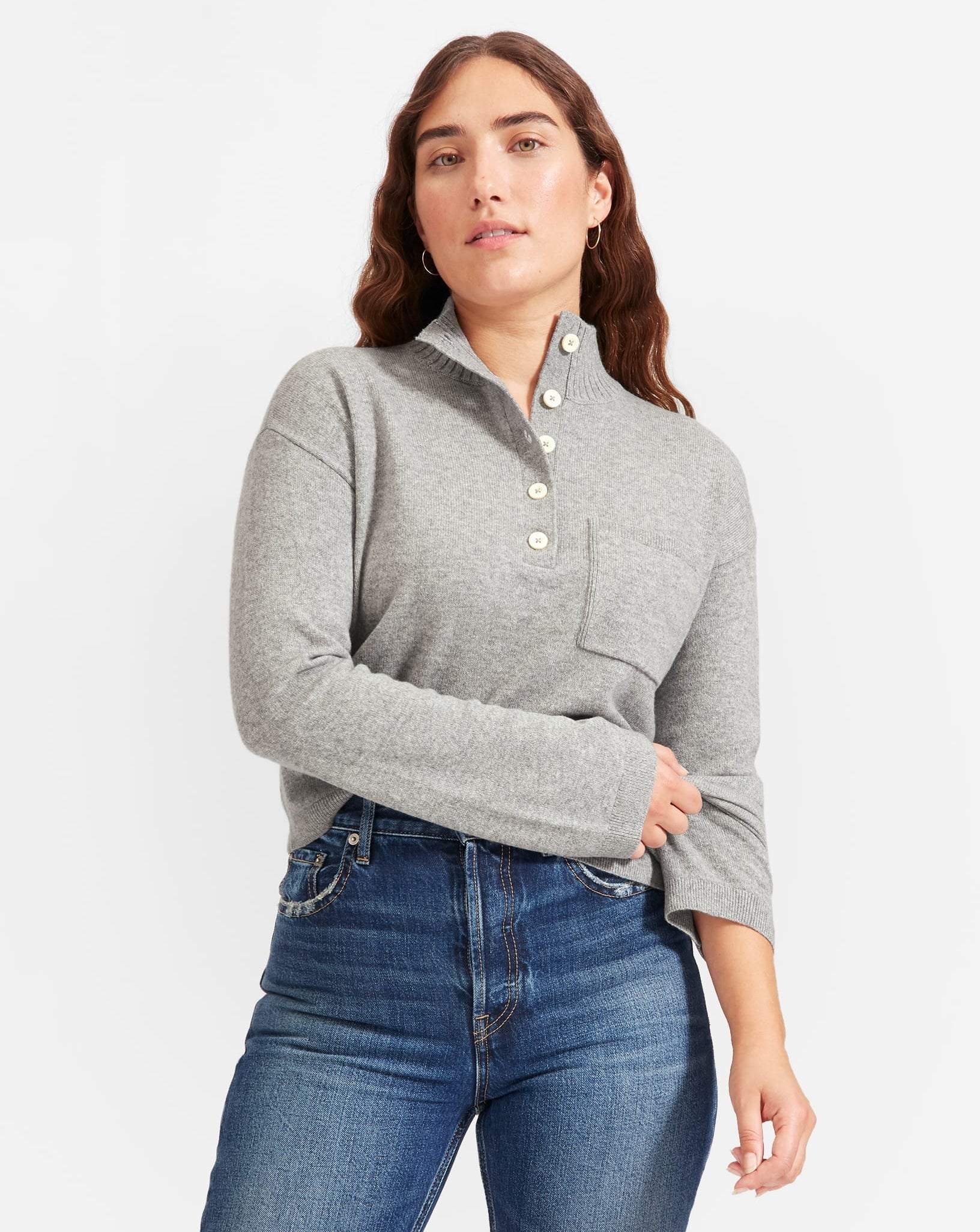 model in light grey long sleeve sweater with henley-style buttons