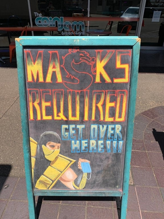Sign featuring Scorpion from Mortal Kombat reading masks required