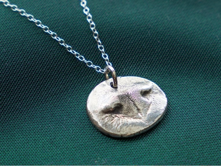 The round silver pendant necklace with a dog nose impression on it