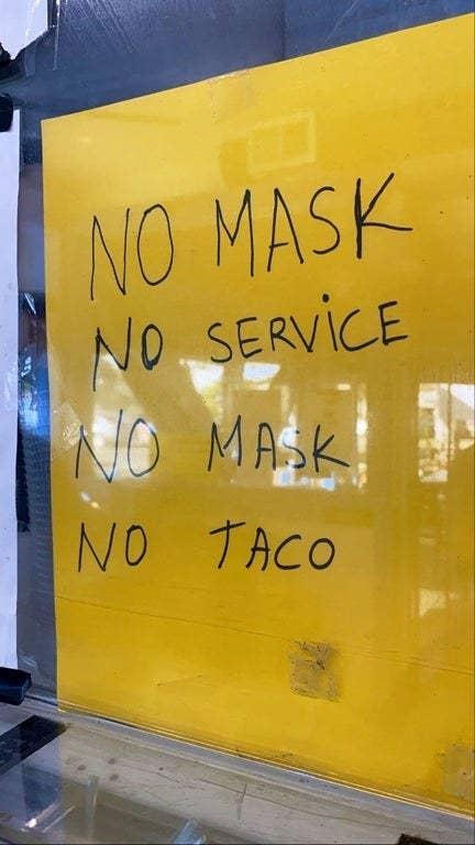 Sign reading no mask no service no mask no taco