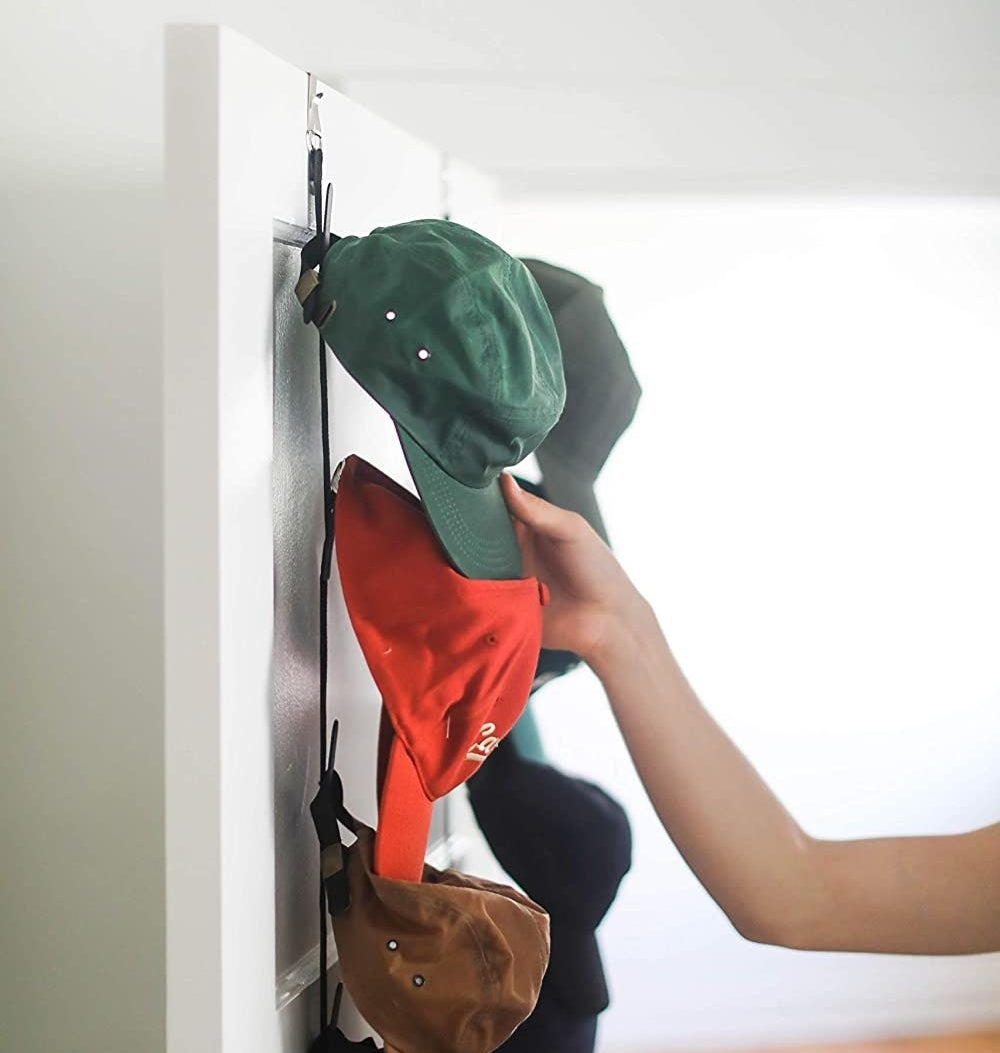 A person hanging their hat on an over-the-door hat rack