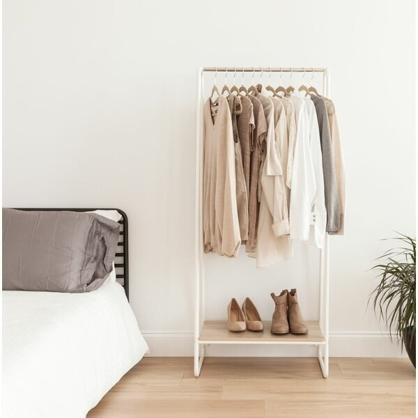 A white and natural wood clothing rack with a small shelf for about three pairs of shoes and enough hanging space for around 13 articles of clothing