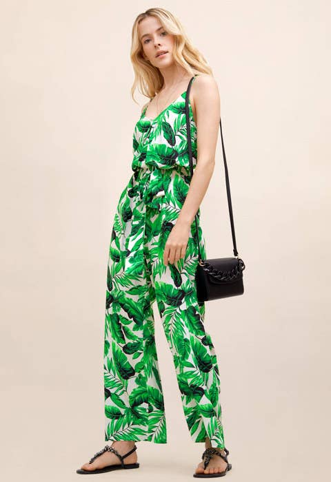 a model in a green leaf covered jumpsuit