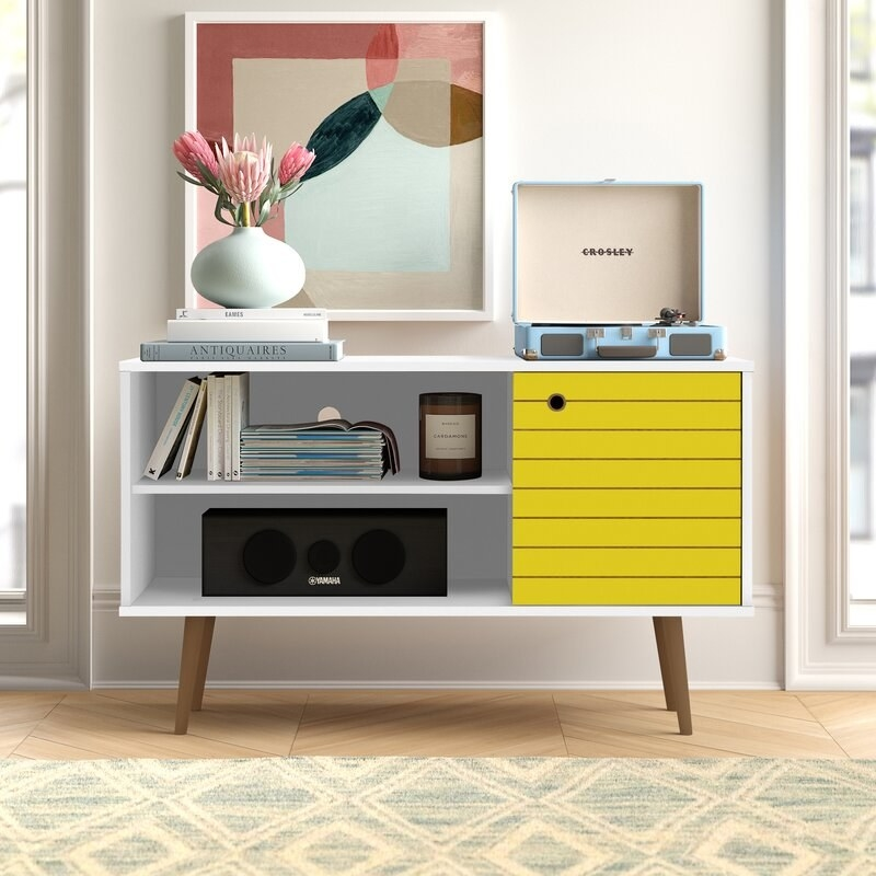 A white television stand wit two shelves, brown legs, and a yellow cabinet door