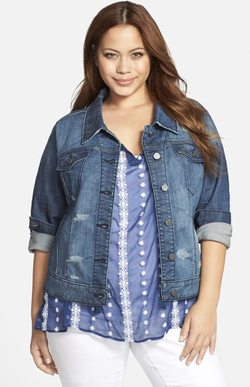 Model wearing the denim jacket with silver buttons and distressing throughout