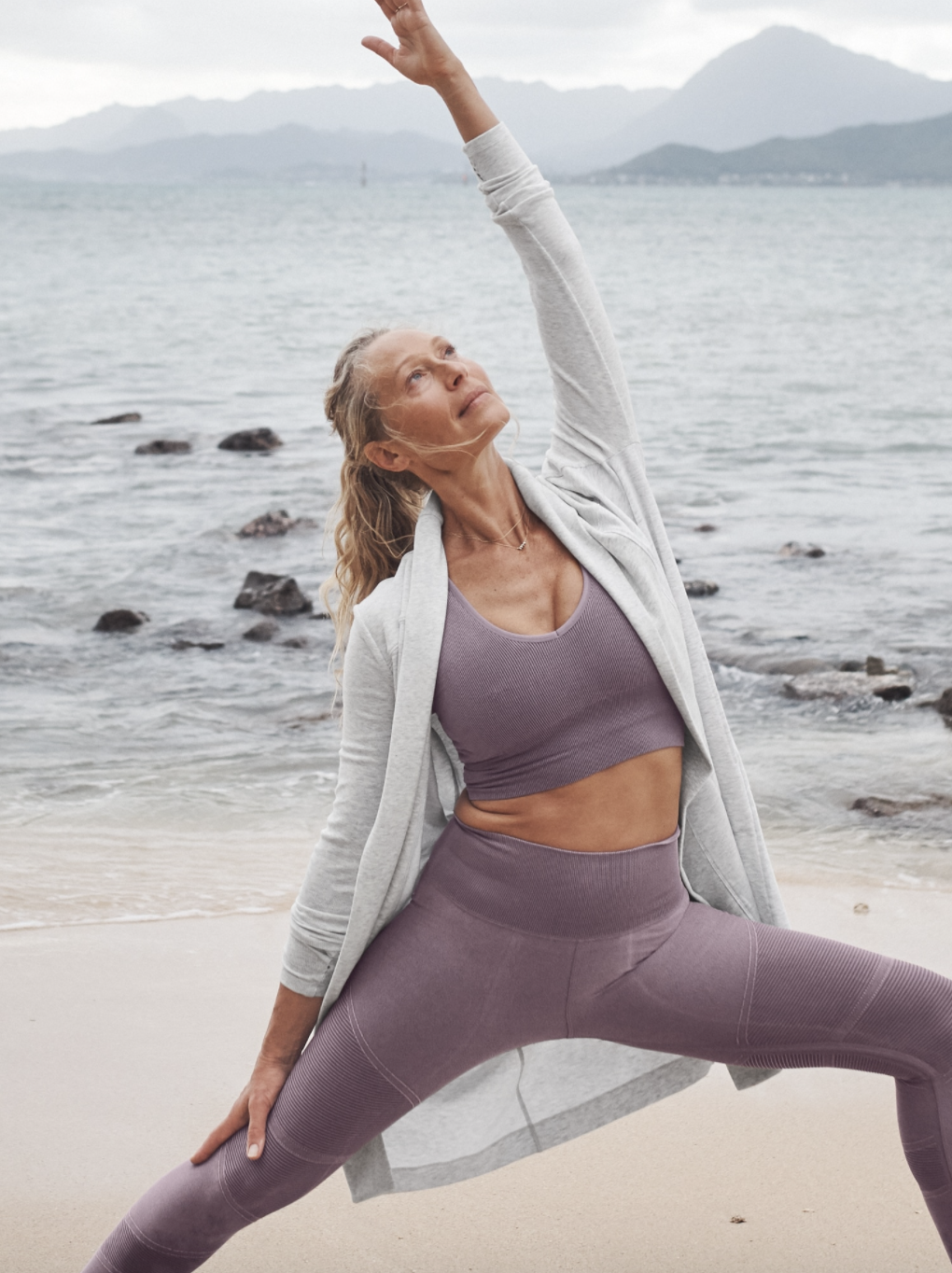 A model wearing the wrap over a sports bra and leggings while doing yoga poses