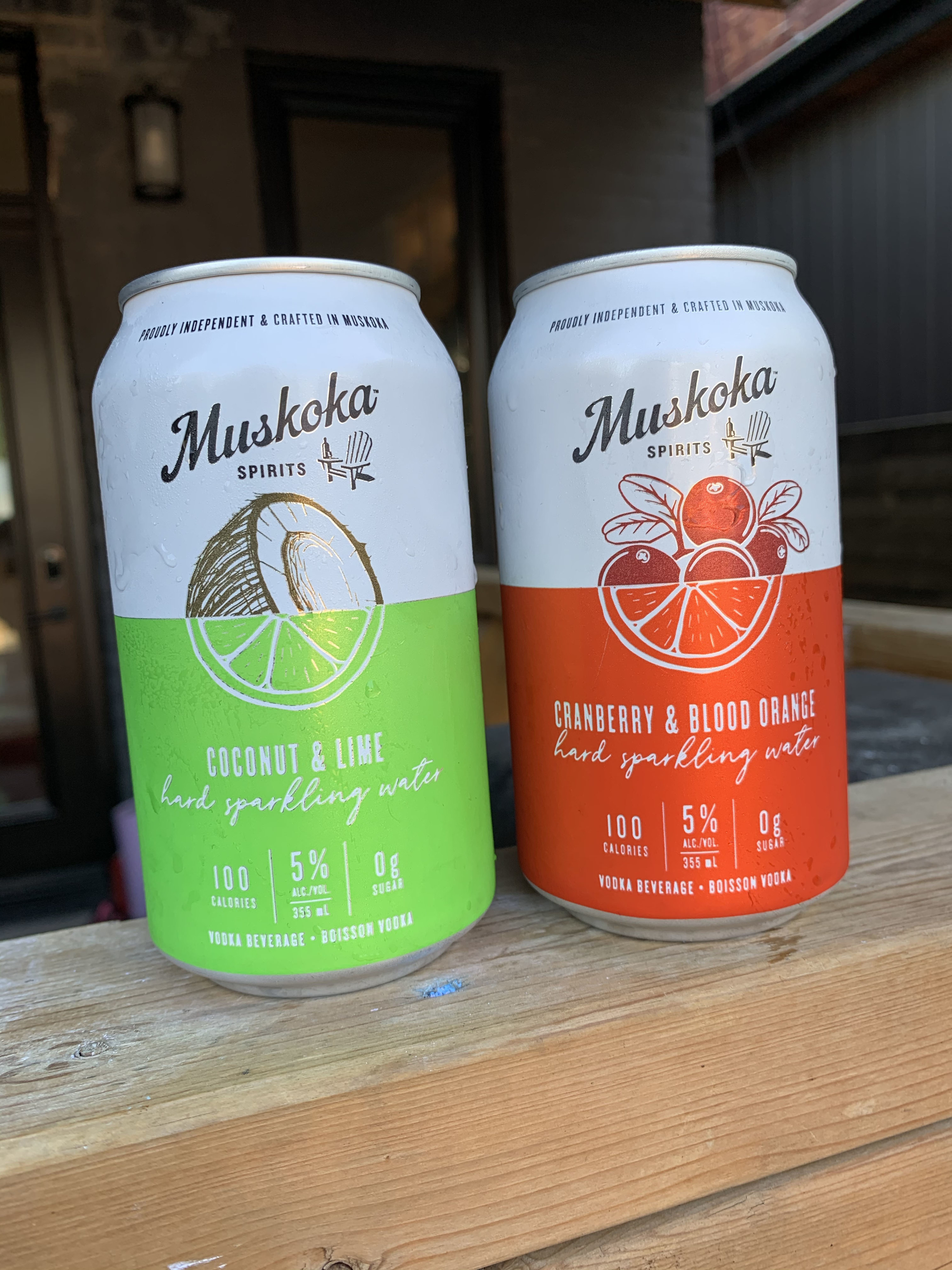 Two cans of Muskoka Spirits – one can is green and white with half an illustration of a coconut intersecting with half a lime. The other can is red and white with half an illustration of cranberry intersection with half an illustration of blood orange.