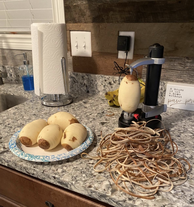 A reviewer image of a peeled potato in the device next to all the peel scraps