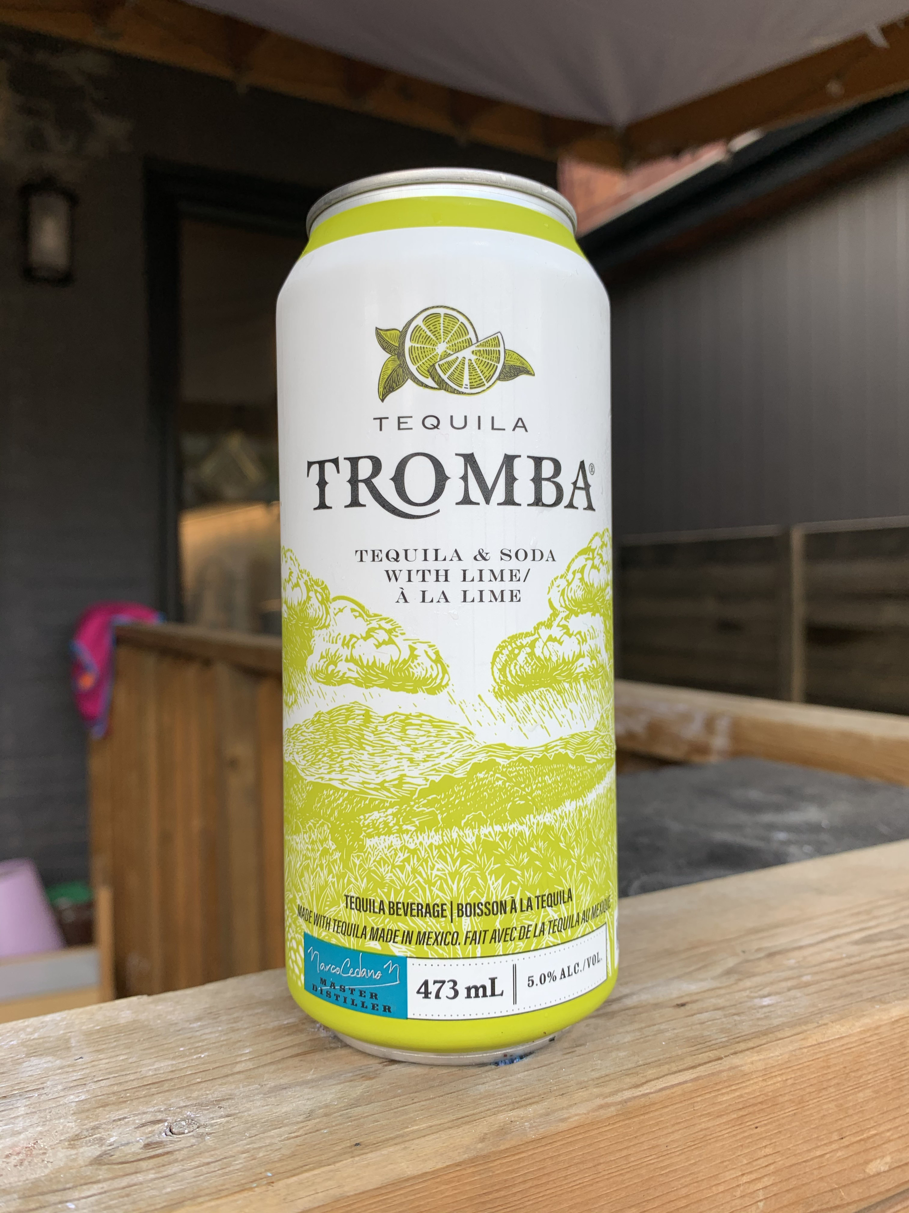 A can of Tequila Tromba with a green landscape illustration on the front of the can with illustrations of limes at the top.
