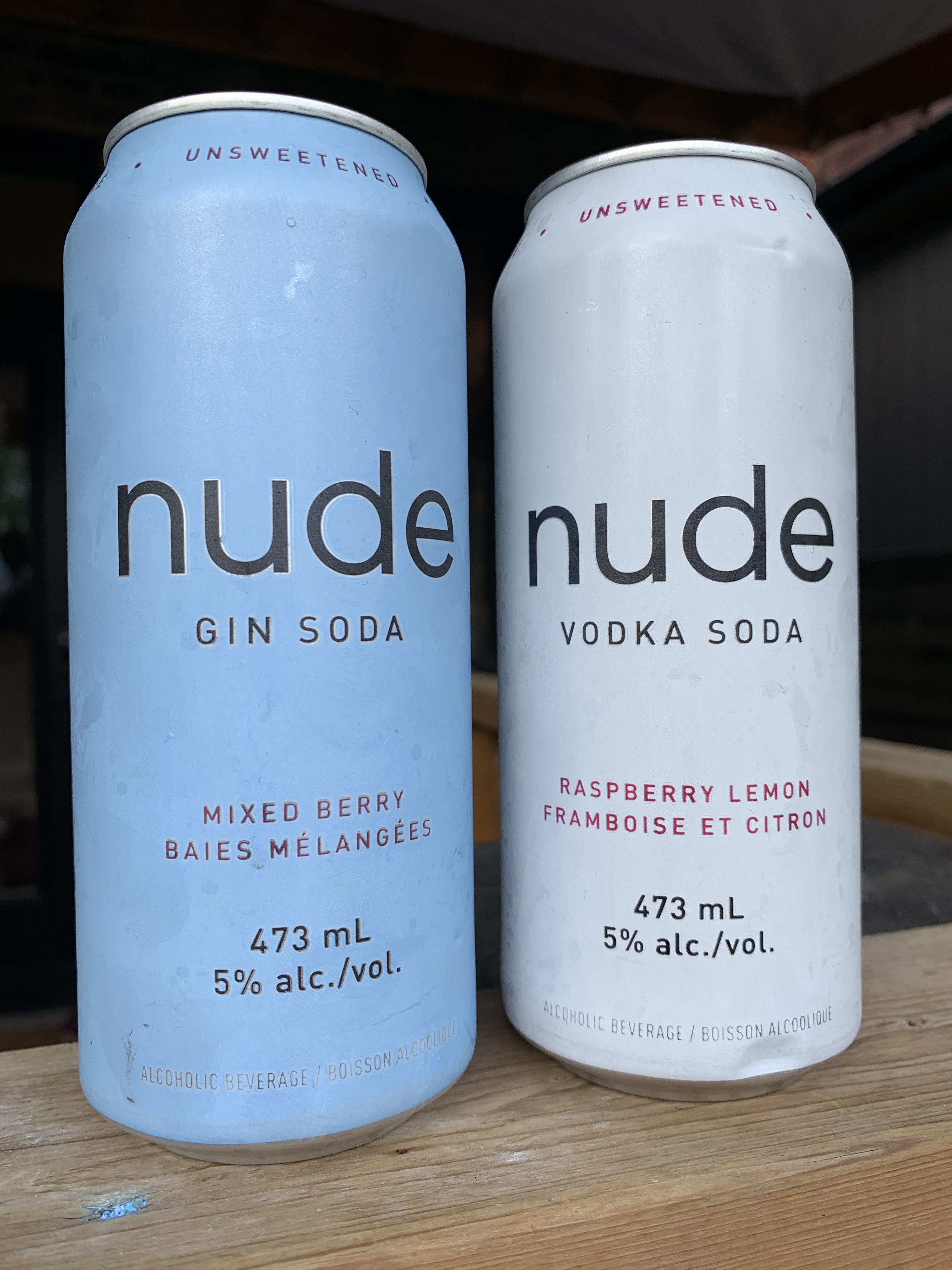 Two cans of Nude – one is blue and is a mixed berry gin soda, while the other is white and is a vodka soda with raspberry lemon.
