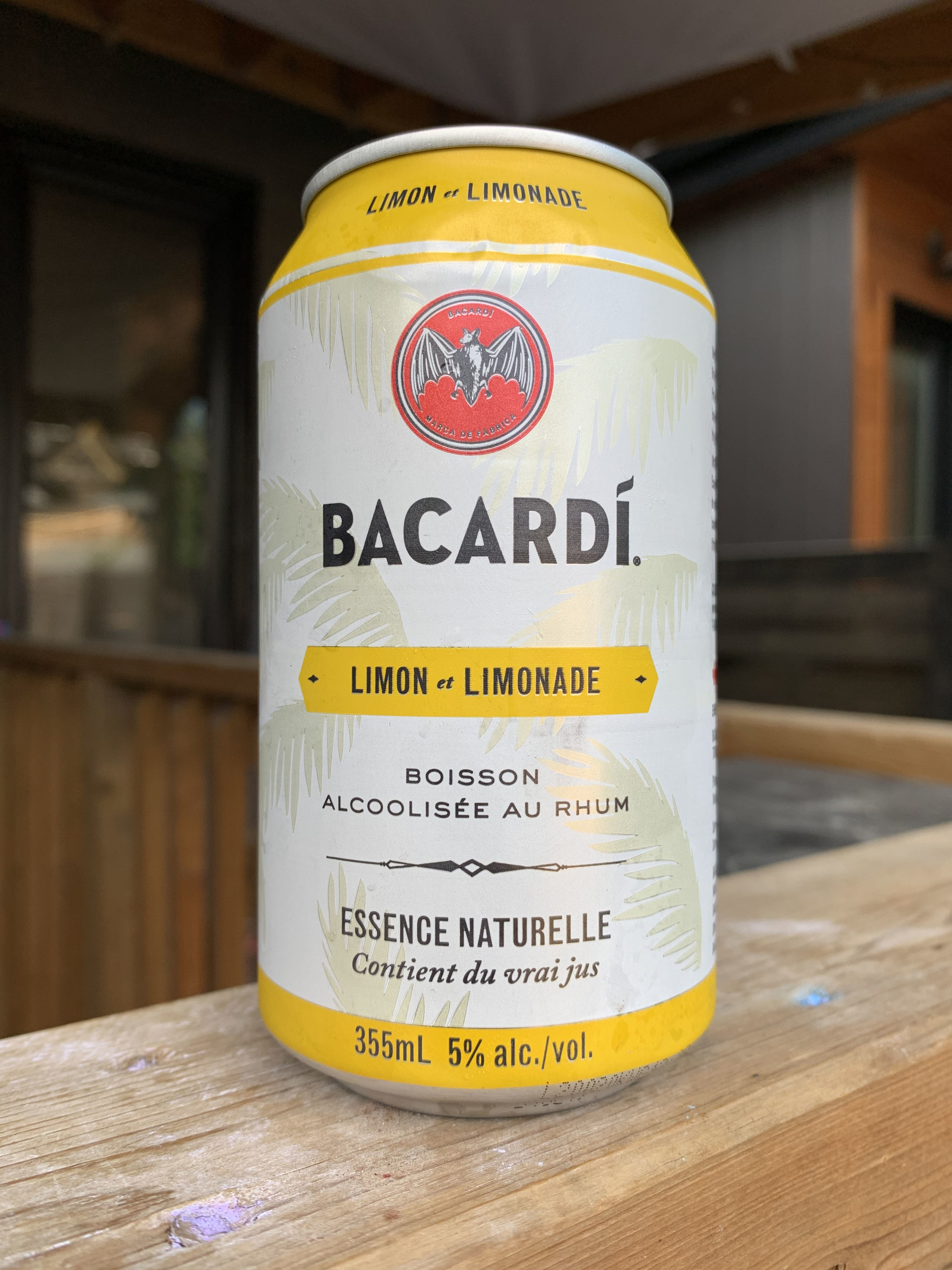 A small can of Bacardi with yellow bands around the can and palm trees in the background.