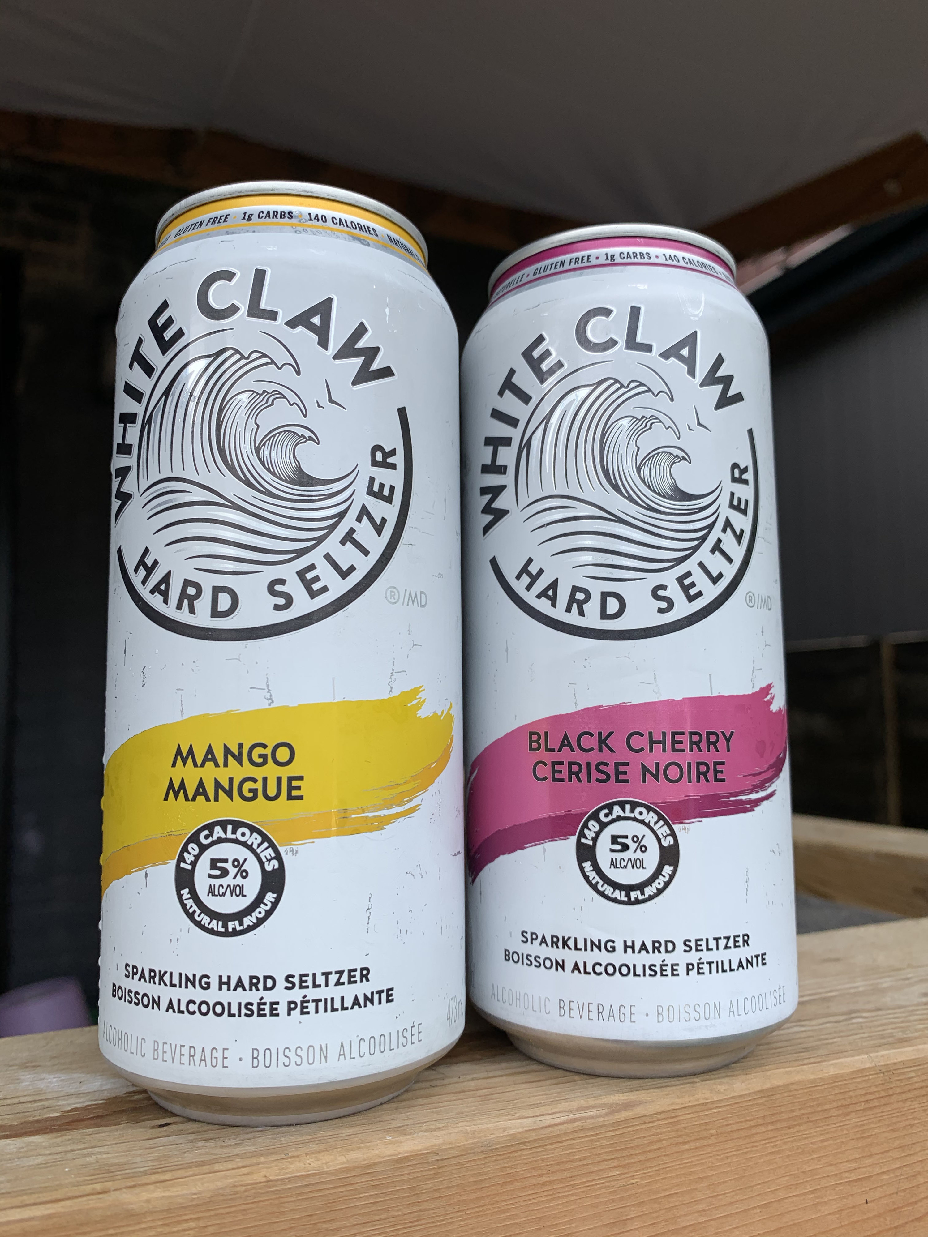 Two cans of White Claw Hard Seltzer, one says mango and one says black cherry.