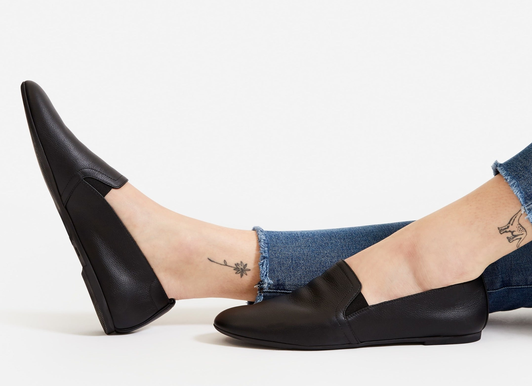 model in black flats with some top coverage and small elastic pieces on the edges of the foot