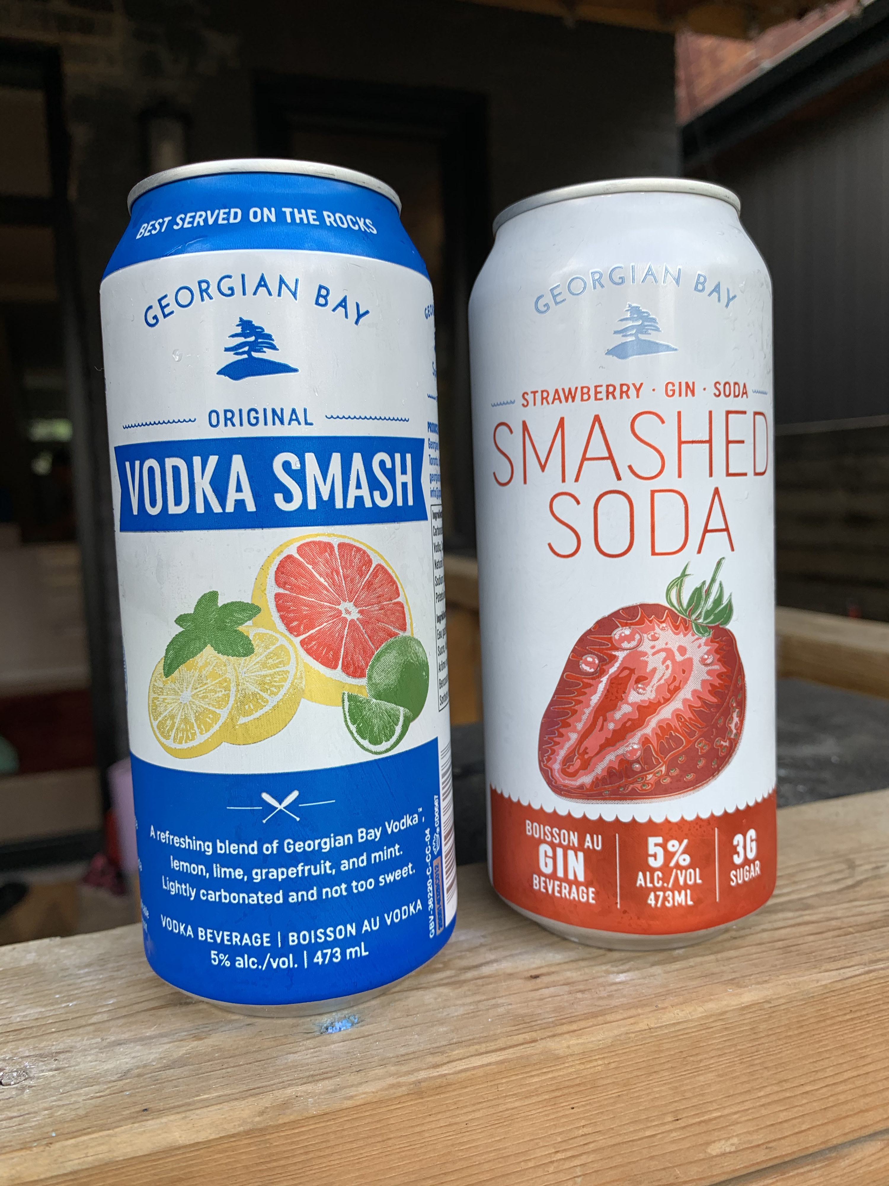 Two cans of Georgian Bay drinks – one is Vodka Smash and is blue and white with citrus illustrations on front, and the other is Smashed Soda (Gin) in red and white with an illustration of a strawberry.