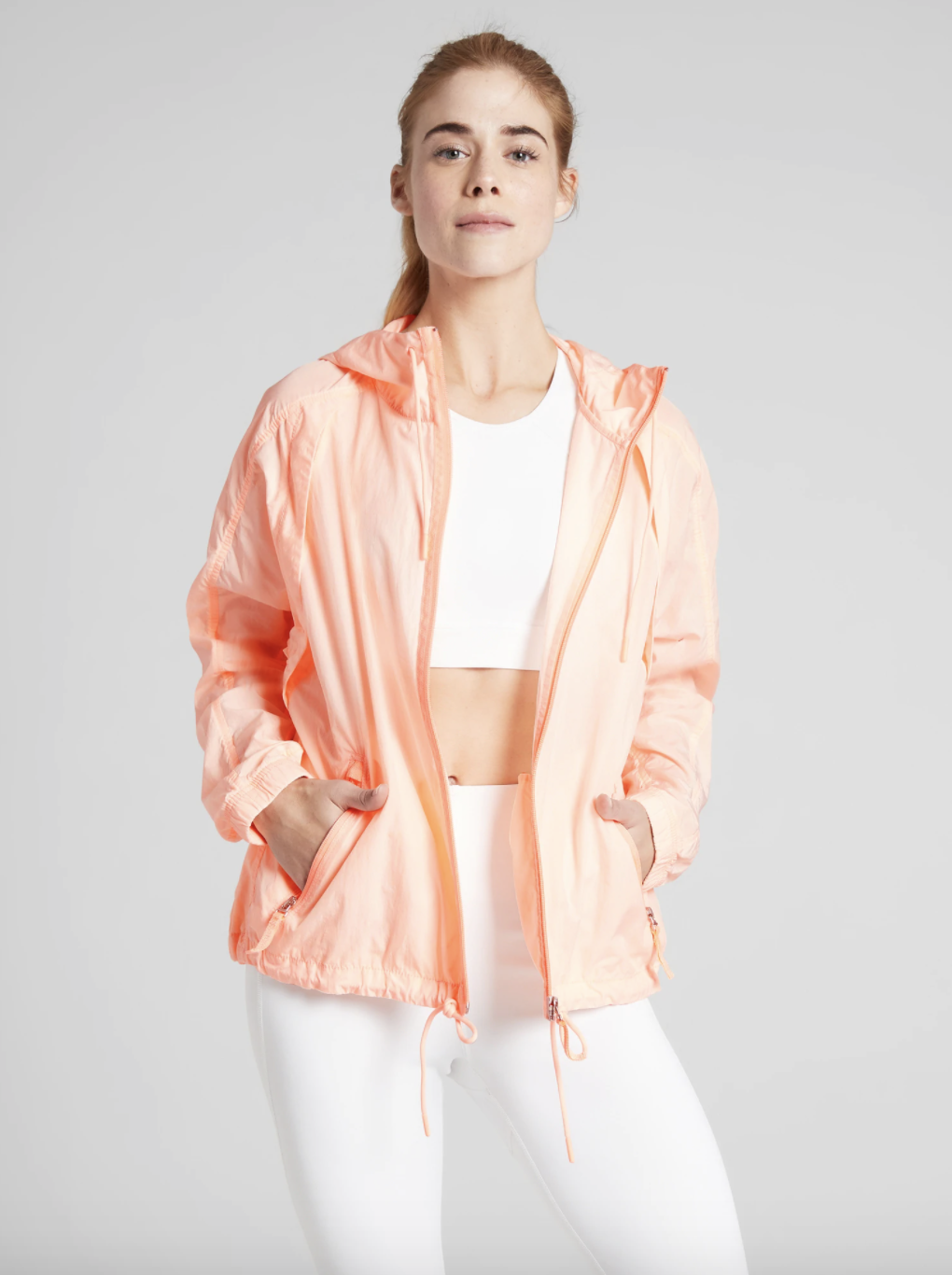 A model wearing the jacket, which has a zipper front, a hood, and side pockets