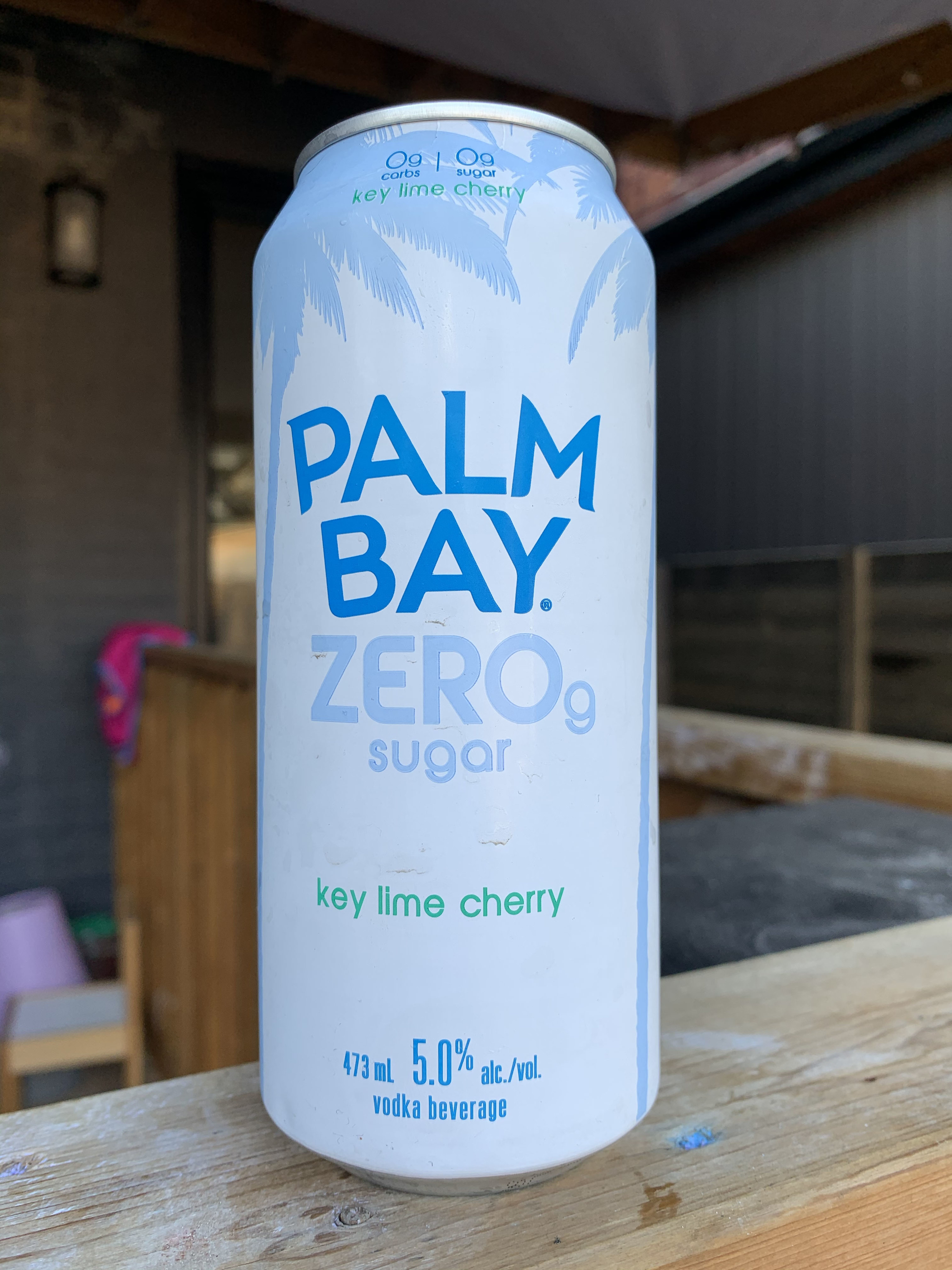 A white and blue can of Palm Bay Zero Sugar Key Lime Cherry with blue palm trees framing the can.