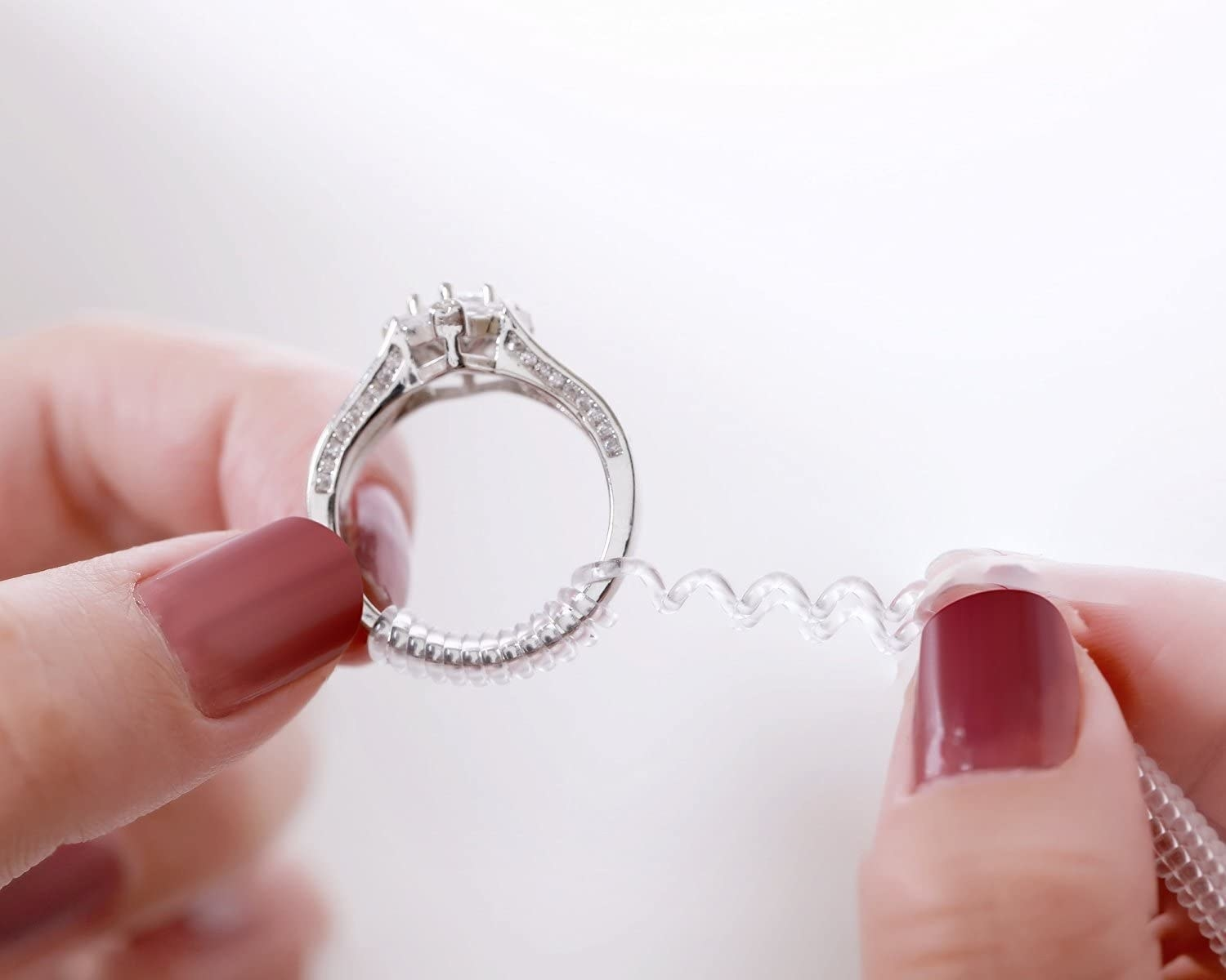 A person putting the ring adjuster onto a diamond ring